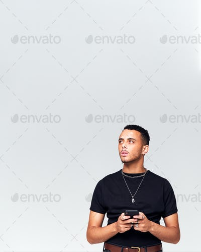 Studio Shot Of Causally Dressed Young Man Using Mobile Phone Looking Off Camera