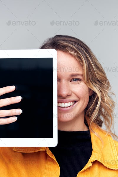 Studio Portrait Of Smiling Young Woman Covering Face With Digital Tablet