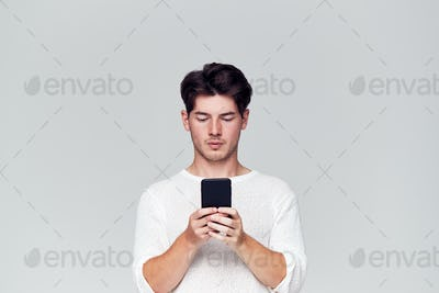 Studio Shot Of Causally Dressed Young Man Using Mobile Phone