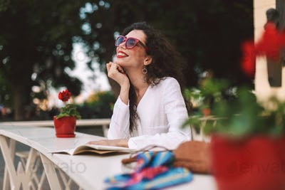 Smiling woman in sunglasses with notepad dreamily looking aside resting in summer terrace of cafe