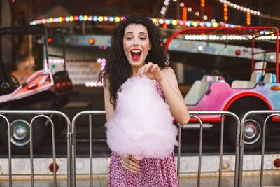 Pretty emotional girl in dress eating pink cotton candy amazedly looking in camera in amusement park
