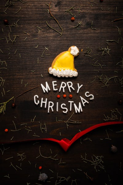 Merry Christmas text with gingerbread Santa Claus hat