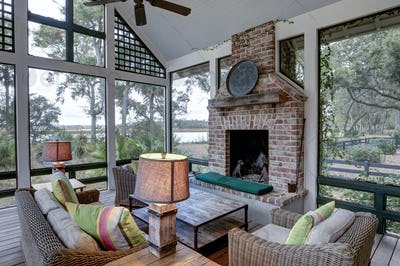 Luxurious three season screen porch with fireplace, looking out onto waterfront property.