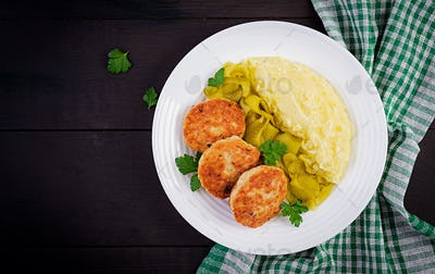 Homemade fried cutlets/meatballs with mashed potatoes and pickled cucumber on white plate.