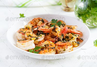 Grilled shrimps. King prawn tails in orange-garlic sauce with parsley.