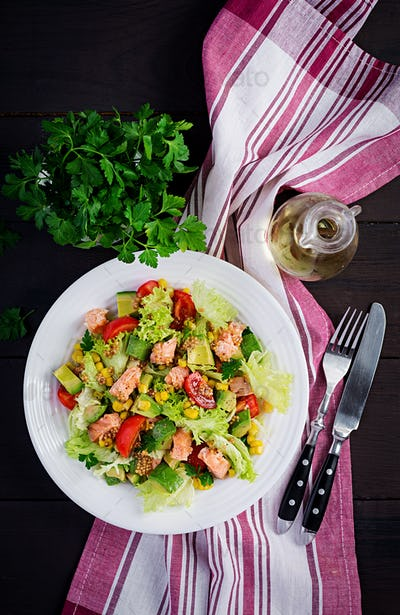 Salad with grilled salmon, lettuce, avocado, tomatoes and corn on a white bowl. Paleo diet.