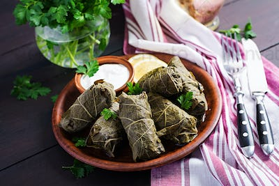 Dolma. Stuffed grape leaves with rice and meat on dark table. Middle eastern cuisine.