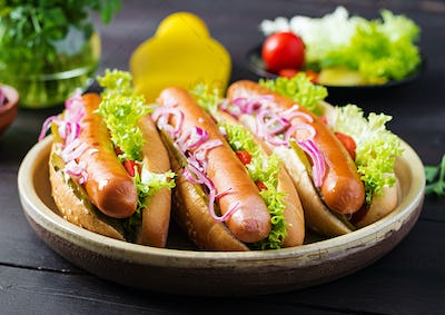 Hot dog with  sausage, pickled cucumber, tomatoes, red onions