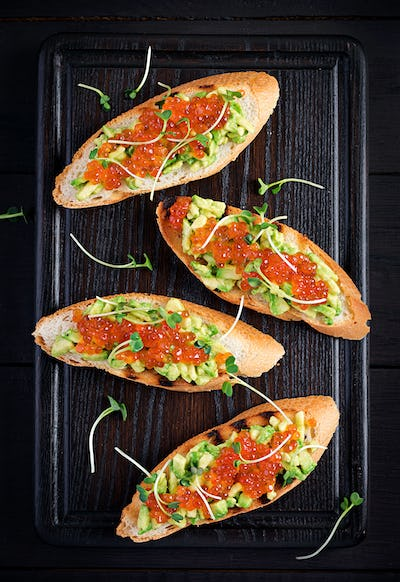 Sandwiches with salmon red caviar and salsa with avocado.