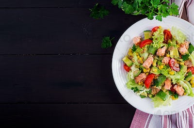 Salad with grilled salmon, lettuce, avocado, tomatoes and corn