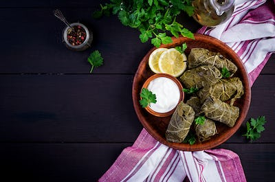 Dolma. Stuffed grape leaves with rice and meat on dark table. Middle eastern cuisin