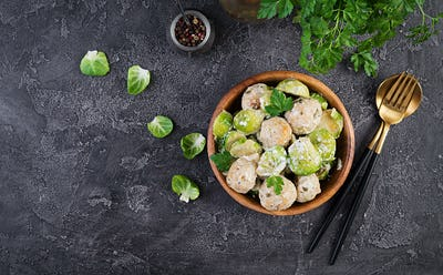 Brussels sprouts roasted with chicken meatballs and onions in a creamy sauce. Top view