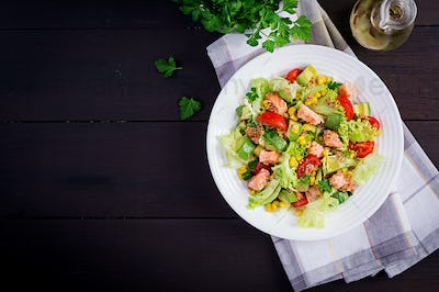 Salad with grilled salmon, lettuce, avocado, tomatoes and corn on a white bowl.