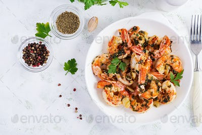 Grilled shrimps. King prawn tails in orange-garlic sauce with parsley. Top view, copy space