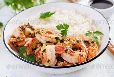 Grilled shrimps and boiled rice. King prawn tails in orange-garlic sauce with parsley.