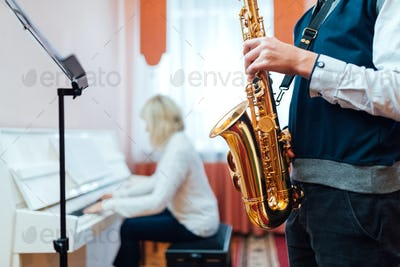 Student saxophone at a lesson in a music school close-up on background of a teacher at the piano