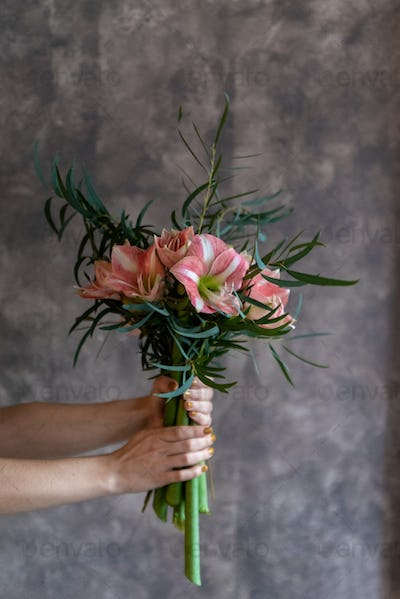 Woman's hands holding a bouquet of flowers, amaryllis