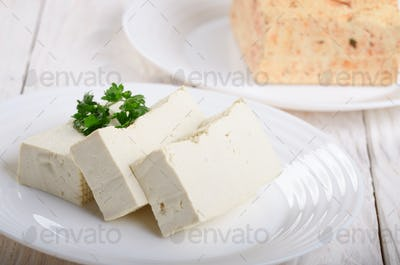 Soy Bean curd tofu on clay dish closeup. Non-dairy alternative substitute for cheese