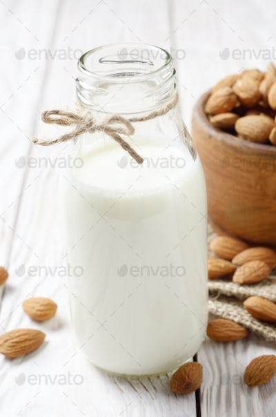 Milk or yogurt in glass bottle on white wooden table with bowl of almonds on hemp napkin aside