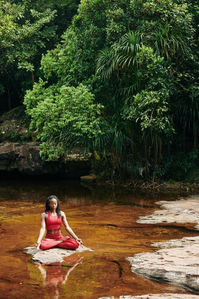 Young woman meditating in forest