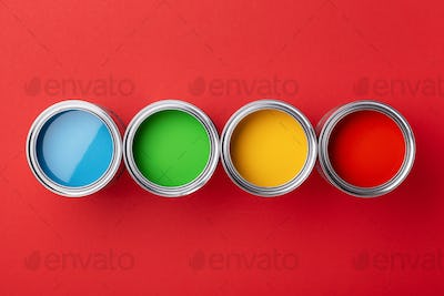 Row of Cans with Colorful Paints on Red Background.