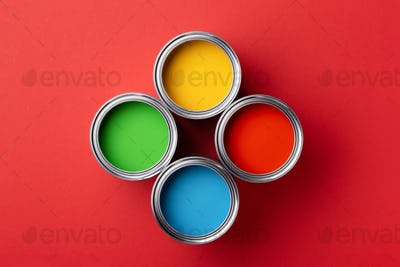 Four Cans of Colorful Paint on Red Background.