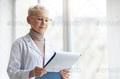 Portrait of Female Doctor Holding Clipboard by Window