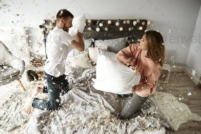 Happy couple during pillow fight among plumage falling