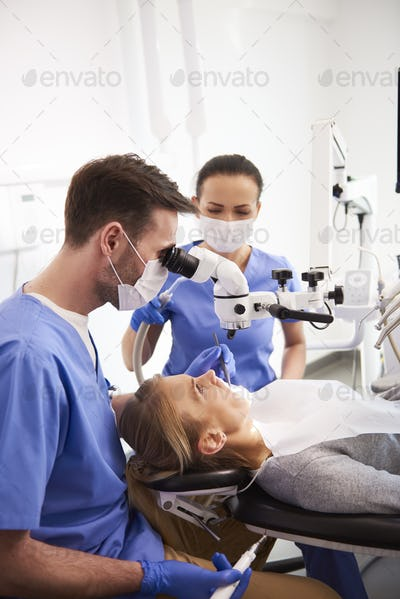 Dentist and his assistant working with dental microscope