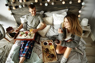 Man and woman eating breakfast on bed