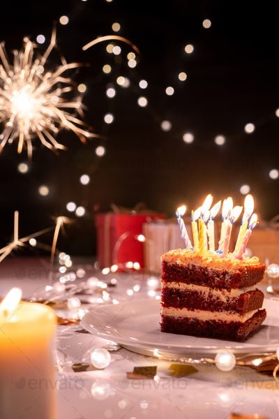 Piece of cake with many burning candles on plate surrounded by sparkling lights