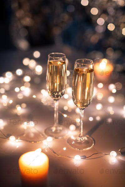 Two crystal flutes of champagne surrounded by lit garlands and burning candles