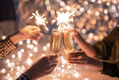 Hands of couple with flutes of champagne and their friends with bengal lights