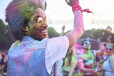 African man in holi colors dancing during music festival