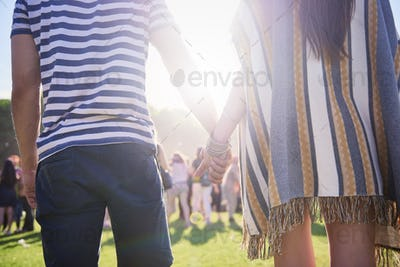 Rear view of couple holding hands in festival