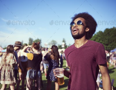 Young African man drinking beer at the festival