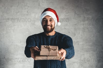 young man shows brown craft paper gift box