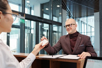 Bald mature businessman in eyeglasses and formalwear taking card from hotel room