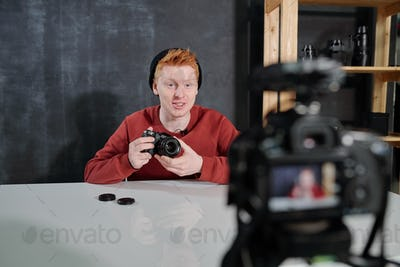 Cheerful young vlogger by desk holding new photocamera while presenting it