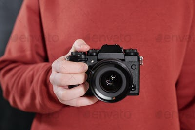 Hands of contemporary male photographer with new photocamera by chest