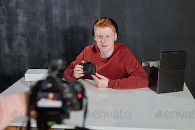 Young man in casualwear sitting by desk and talking about new photocamera