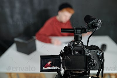 Screen of video camera in front of young male vlogger sitting by desk