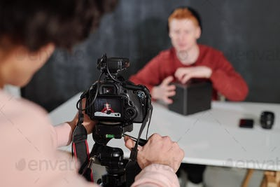 Hands of young operator by camera shooting contemporary male vlogger