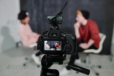 Screen of digital video camera with two vloggers sitting on chairs and talking