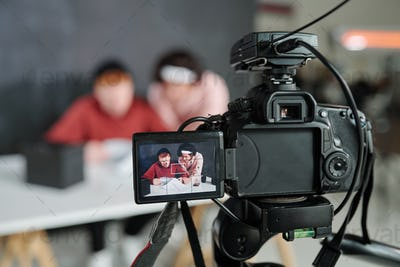 Two young contemporary male vloggers on screen of video camera in studio