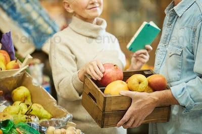 Smiling Senior Couple Holding Box of Apples at Market