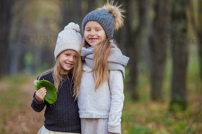 Little adorable girls outdoors at warm autumn day