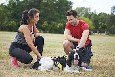 Couple and dog resting after workout on the fresh air
