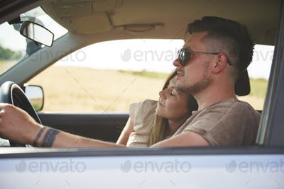 Loving young couple traveling by car