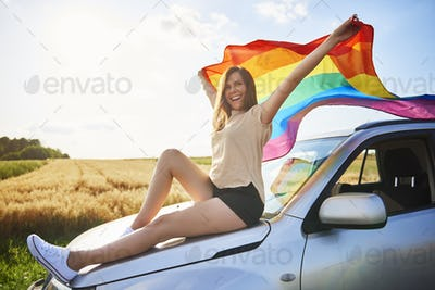 Portrait of young woman waving rainbow flag
